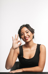 Pretty young asian woman sitting at the table