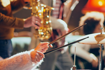 Close up of Caucasian woman holding drumsticks and playing drums. Home studio interior.