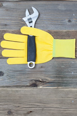 yellow safety glove and a pipe wrench