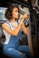 mechanic woman in a blue overalls repair with a screwdriver the door of car
