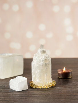 Naturally carved mineral stone Selenite tower has healing on cleansing properties. Candle holder, piece of raw and carved Selenite tower on dark wooden table, orange bokeh background.