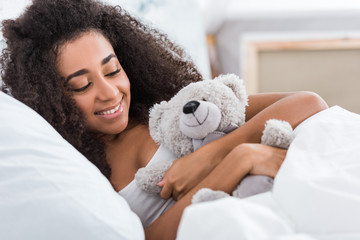 close up view of smiling african american curly girl laying in bed with teddy bear at home