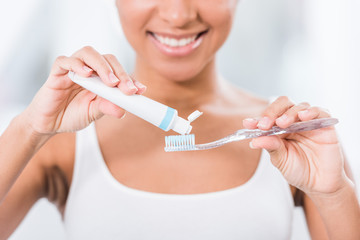 partial view of young woman putting toothpaste on toothbrush