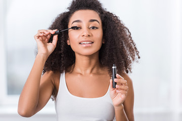 curly african american girl using mascara and looking at camera