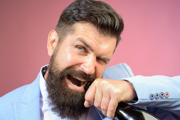 Brutal handsome man opens his teeth bottle of champagne. Champagne or wine bottle. Sexy male model pulls out cork with teeth with bottle of wine. Bearded man trying to open bottle of wine. Bad habits.