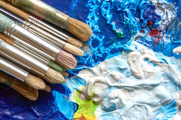 Old used paint brushes with wooden handles on palette with acryllic paint in different colours and copy space