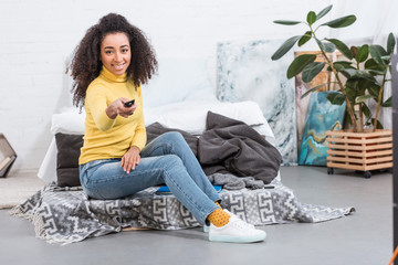 cheerful stylish african american girl using remote controller and watching tv at home