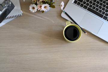 Top office wood table with cup of coffee, notebook, pencil, laptop and copy space