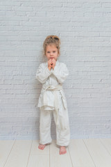 girl, a child in a kimono on karate training works out blows and greeting