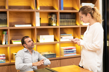 Female student answering with digital tablet to her professor. Mid adult bearded executive sitting at table in his office, having meeting with young female employee. University or apprentice concept