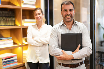 Portrait of confident mid adult executive with secretary standing behind. Caucasian bearded man holding folder, looking at camera and smiling in his office. Success concept