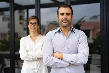 Portrait of confident mid adult male leader with female colleague. Caucasian entrepreneur standing and looking at camera, female employee standing behind. Business leader concept