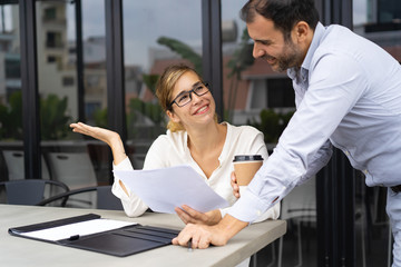 Portrait of happy business colleagues discussing papers at coffee break. Young Caucasian businesswoman wearing glasses sitting at table and talking to bearded male colleague. Planning concept