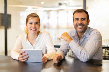 Portrait of happy colleagues sitting at cafe during break. Young Caucasian businesswoman with pc tablet and mid adult businessman sitting at table, looking at camera and smiling. Colleagues concept