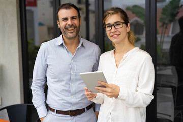 Portrait of happy mid adult businessman and young businesswoman wearing glasses standing together, looking at camera and smiling. Woman holding digital tablet. Team concept