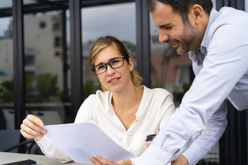 Portrait of smiling male and female managers discussing papers. Young Caucasian businesswoman wearing glasses sitting at table and talking to bearded male colleague. Teamwork concept