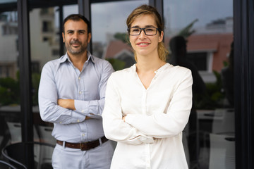 Portrait of smiling successful female leader wearing glasses, her mid adult male colleague standing behind. Businesspeople posing in office. Female leader concept