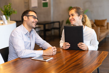 Smiling female manager having meeting with male executive. Mid adult hr manager wearing glasses having job interview with young woman. Employment or meeting concept