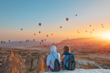 Hot air balloon flying over spectacular Cappadocia - Girls watching the hot air balloon at the hill of Cappadocia