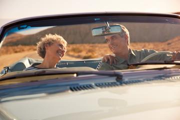 Senior couple on a US road trip, seen through car windscreen