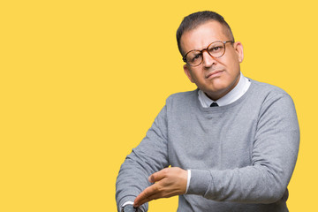 Middle age bussines arab man wearing glasses over isolated background In hurry pointing to watch time, impatience, upset and angry for deadline delay