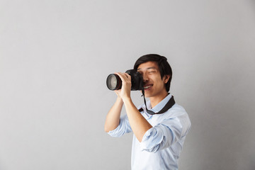 Happy asian man standing isolated over gray