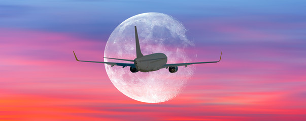 """Passenger airplane in the sky against super moon at sunset """"Elements of this image furnished by NASA """""""