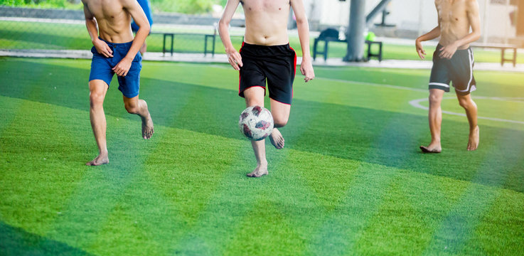 Soccer players not wearing a sport shirt and barefoot do trap and control the ball for shoot to goal