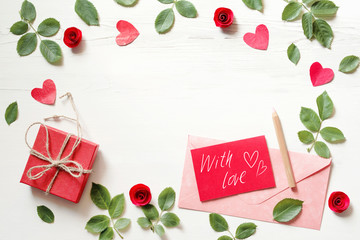 """Red card with an inscription """"With love"""", hearts, gift box and pink envelope on a white wood background, top view. Romantic background by St. Valentine's Day"""