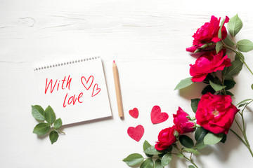 """White notebook with an inscription """"With love"""", hearts and bouquet of red roses on a white wood background, top view. Romantic background by St. Valentine's Day"""