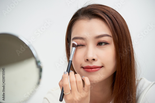 459b434dd Close up of beautiful face of asian young woman getting make-up. Asian woman  is applying eyeshadow on her eyebrow with brush. Beautiful girl look at  mirror ...