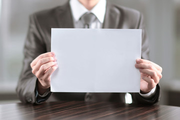 close up.businessman showing blank sheet of paper