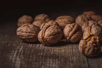 close up view of walnuts on wooden tabletop on black backdrop