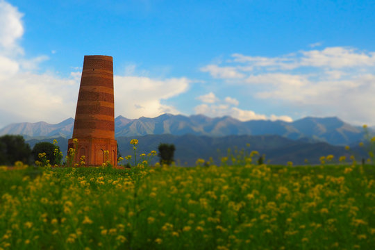Ancient oriental tower against a background of snow-capped mountains and blue sky