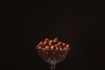 close up view of shelled hazelnuts in glassware on black backdrop