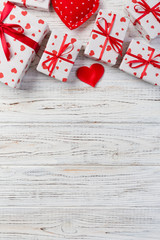 Valentine or other holiday handmade present in paper with red hearts and gifts box in holiday wrapper. Present box of gift on white wooden table top view with copy space, empty space for design