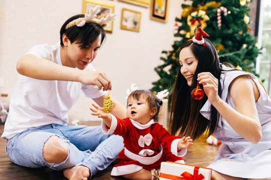 Asian father and Caucasian mixed mother with little daughter in santa claus costume and Christmas tree in background happily playing at home