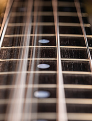 Close up of a bass guitar string and fingerboard with strings vibrating