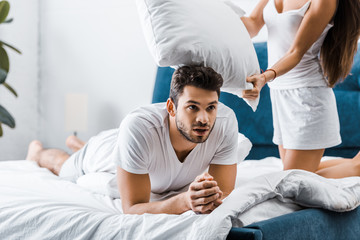 handsome exhausted young man resting in bed after pillow fight