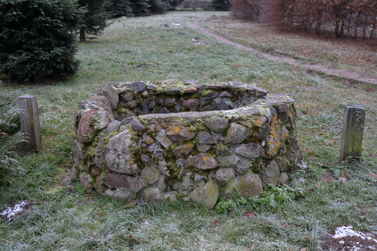 Old hidden manhole from the cobblestones among the grass and dry fallen leaves