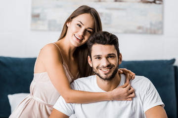 young attractive woman hugging boyfriend and smiling while sitting on bed