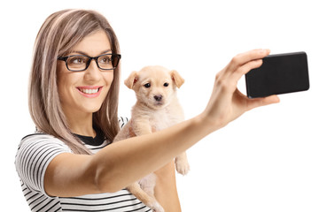 Young woman holding a cute puppy dog and taking a selfie