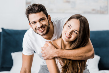 young happy man hugging girlfriend and smiling cheerfully