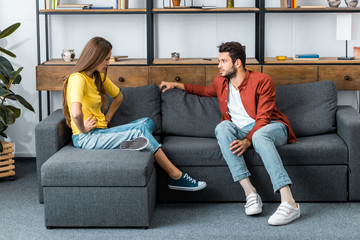 boyfriend and girlfriend quarreling on sofa in living room