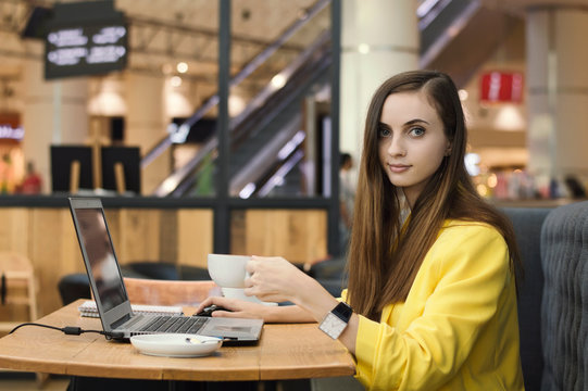 Young female freelancer in yellow jacket working in a cafe with laptop and drinking coffee. Freelance work. Blogging and writing content