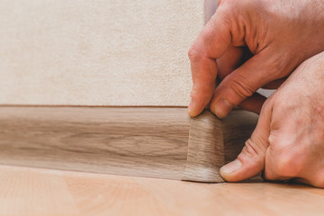 Technology of installation and installation of plastic floor plinth - Master sets the outer corner on the baseboard