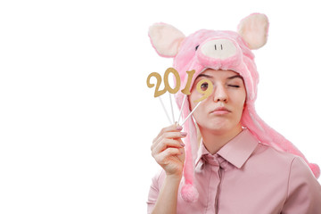 young girl in a pig costume holding in her hands the numbers 2019, looks in, isolated on white background