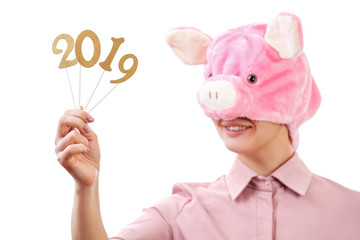 girl in the image of a pink pig, smiling, showing figures for 2019. New Year. Portrait, isolated on a white background