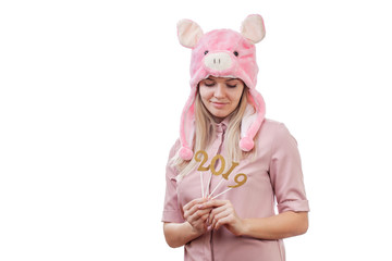 beautiful girl in a pig costume holds figures 2019 in her hands, look, waiting for the New Year. Copy space