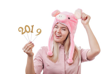funny girl in a pig hat, make a face, shows tongue, shows figures 2019. New Year. Isolated on white background. Copy space.